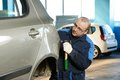 Auto repair man flatten metal body car worker and align with hammer in automotive industry Stock Photography