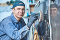Auto repairman grinding autobody bonnet Royalty Free Stock Photo