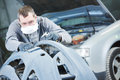 Auto repairman grinding autobody bonnet Royalty Free Stock Photo