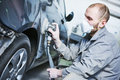 Auto repairman grinding automobile car body Royalty Free Stock Photo
