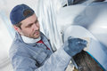 Auto repairman plastering autobody bonnet Royalty Free Stock Photo