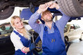 Auto service center crew near car repairing a broken Royalty Free Stock Images