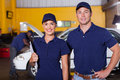 Auto service employees two happy center portrait inside workshop Stock Images