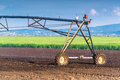 Automated farming irrigation sprinklers system in operation on cultivated agricultural field on a bright sunny summer day Stock Image