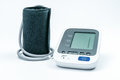 Automatic portable blood pressure machine with arm cuff on white, studio shot.