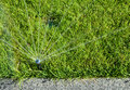 Automatic Sprinkler head spraying water over green grass. Royalty Free Stock Photo
