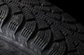 Automobile tire on black background the a Stock Images