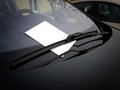 Automotive ad blank white paper under the windshield wipers Stock Photos
