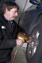 Automotive technician uses pneumatic impact wrench auto repair b ed takes the lug nuts off for a routine brake check Royalty Free Stock Photos
