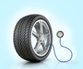 Automotive wheel with a pressure sensor on blue background Royalty Free Stock Photos