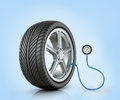 Automotive wheel with a pressure sensor on blue background Royalty Free Stock Photography
