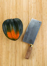 Autumn acorn squash with butcher knife on cutting board vertical photo of single large natural bamboo Stock Photos
