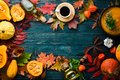 Autumn background with coffee, pumpkin, autumn leaves. flat lay. On a blue wooden background. Top view.