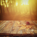 Autumn background of fallen leaves over wooden table and forest backgrond with lens flare and sunset Royalty Free Stock Photo