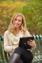 Autumn blond with tablet ii a pretty enjoying her on an day Royalty Free Stock Photo