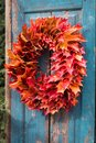Autumn colorful maple leaves wreath on the blue rustic door Royalty Free Stock Photo