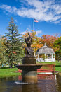 Autumn colors in a city park white gazebo water fountain statue bridge and us flag on sunny day Royalty Free Stock Image