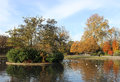 Autumn colors on trees in the regent s park london view across part of lake england to and their reflections with Stock Image