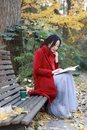 Young asian sensual woman reading a book sit bench in romantic autumn scenery.Portrait of pretty young girl in autumnal forest Royalty Free Stock Photo