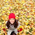 Autumn fall leaves background with woman happy looking up sitting on in colorful forest foliage beautiful girl Stock Images