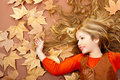 Autumn fall little blond girl on dried tree leaves Stock Image