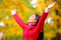Autumn fall woman happy in free freedom pose with arms raised up towards the sky with smiling cheerful elated expression of Royalty Free Stock Photos