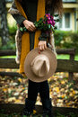 Autumn fashion details hat wool scarf fur vest and bouquet of flowers in her hand woman stand in park near the wooden fence Stock Photography