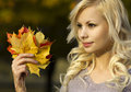 Autumn fashion girl blonde beautiful young woman with yellow maple leaves in hand outside fall Royalty Free Stock Image