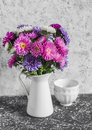 Autumn flowers asters in a white pitcher on a light background. Royalty Free Stock Photo