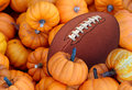 Autumn football thanksgiving day and sports during harvest time with a holiday tournament ball in a pile of orange pumpkins as a Royalty Free Stock Photos