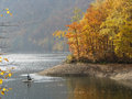 Autumn forest with lake and fisherman Stock Photos