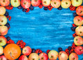 Autumn frame of apples, pumpkin, rowan on  painted blue wooden b Royalty Free Stock Photo