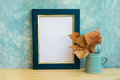 Autumn frame mockup, blue and golden border, tree branch with dry leaves in pitches, bluish concrete wall background, rustic Royalty Free Stock Photo