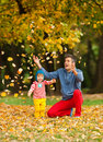 Autumn fun father and son playing outdoors throwing yellow leaves in the air dressed in colorful clothes Royalty Free Stock Images