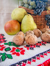 Autumn harvest of grapes walnuts pears and apples on a traditional towel romanian Royalty Free Stock Photo