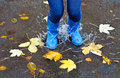 Autumn jumping woman with blue rubber boots Stock Photos