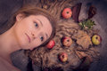 Autumn lady with rich harvest in her golden hair portrait of beautiful girl leaves and apples gorgeous lying over canvas material Royalty Free Stock Photos