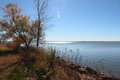 Autumn at the lake nearly bare trees blue sky and blue waters of waconda in fall Royalty Free Stock Photo