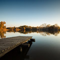 Autumn lake scene with wooden dock Stock Photos