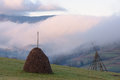 Autumn landscape with haystacks and fog in the mountains Royalty Free Stock Photo