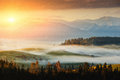 Autumn landscape image with sunrise or sunset, beautiful fog on meadow and mountain on background