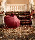 Autumn leaf fall. Red and yellow leaves on the destroyed old stone steps burgundy marsala color umbrella and hat Royalty Free Stock Photo