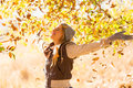 Autumn leaves falling on happy young woman in forest Stock Images