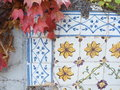 Autumn leaves with floral tiles pending on a decorated wall Stock Photography