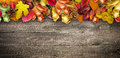 Autumn Leaves over a Natural Dark Wooden background. Old dirty wood tables or parquet Royalty Free Stock Photo