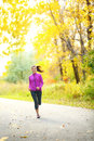 Autumn lifestyle woman running in fall forest with beautiful yellow leaves foliage full length portrait of runner jogging outdoor Royalty Free Stock Images