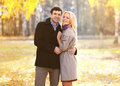 Autumn love relationships and people concept beautiful couple young walking in sunny park Royalty Free Stock Photography