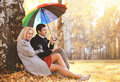 Autumn love relationships and people concept lovely couple with colorful umbrella in the park Stock Image