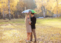 Autumn love relationships and people concept lovely couple young with colorful umbrella walking in the park Stock Images