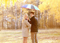 Autumn love relationships and people concept lovely couple young with colorful umbrella walks in the park Royalty Free Stock Image